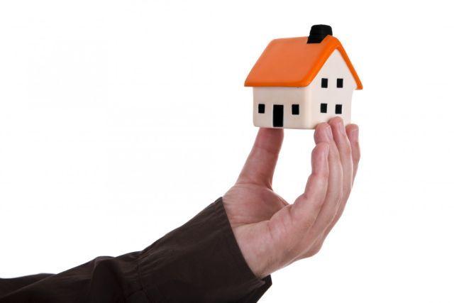 Muž držiaci v ruke dom